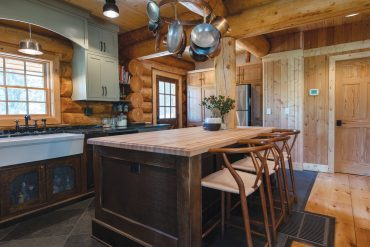 A wooden butcher block-topped island and metal hardware embolden the look of this Spokane log cabin.
